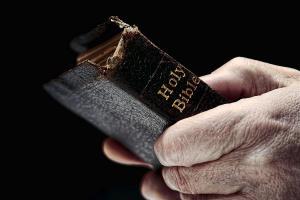 man-hands-holding-old-bible-olivier-le-queinec